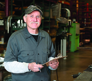 A, Caucasion, senior adult male manufacturing employee poses for the camera with his clip board. He is checking production times.
